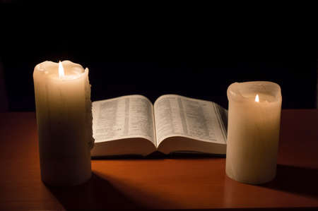 christian candle: table with an open Bible with candlelight Stock Photo
