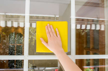 Woman cleaning glass outdoor with a yellow cloth