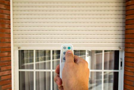 verjas: mano presionando un mando a distancia para controlar un persiana el�ctrica