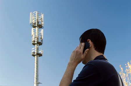 man using a mobile next to a phone mast photo