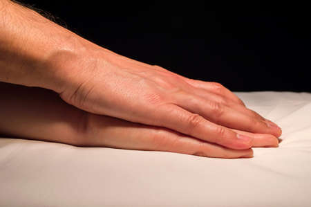 Nahaufnahme von einer Hand der beiden Liebenden im Bett photo