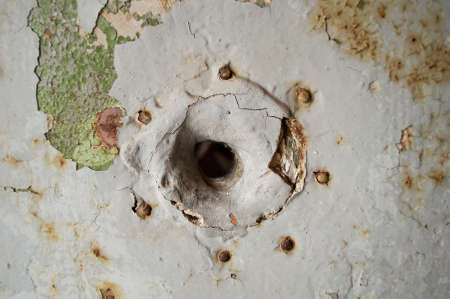close up of a peep hole in grunge metal the door of an old prison