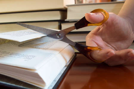 academia: hand with scissors cutting book and being censured Stock Photo
