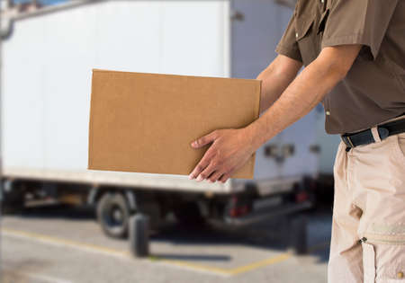 man handing out cardboard box with a truck photo