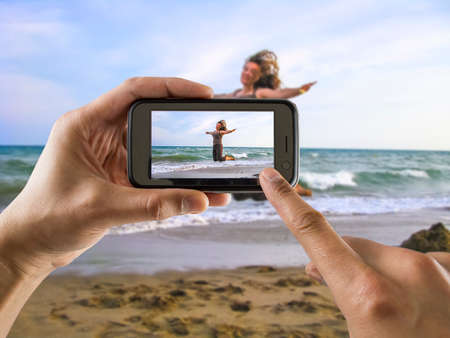 picture person: man taking a picture with your mobile phone a one woman jumping for joy on the beach Stock Photo