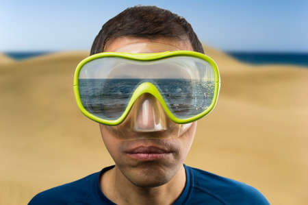 beach hunk: man looking at sea and reflected in the glasses with focus on glasses Stock Photo