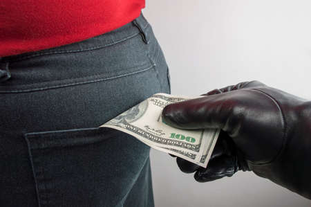 close up of a the hand of a thief stealing the dollars us to a woman photo