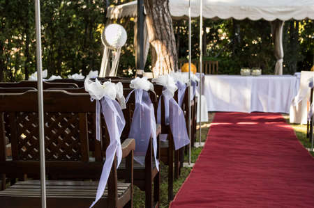 detail of a white ribbon on a chair at a wedding photo