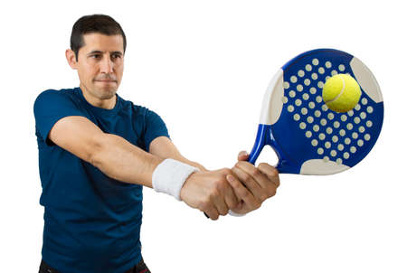 portrait of a young male paddle tennis player standing and swatting the ball