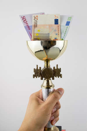 hand lifting a trophy with euros in concept more money more titles with white background photo