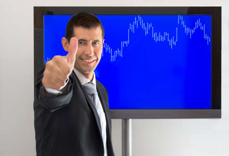 confirms: businessman with thumb up on the successful launch of your business and a graph confirms Stock Photo