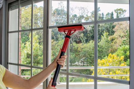 limpiadores: Mujer limpiando cristal de la ventana con vapor