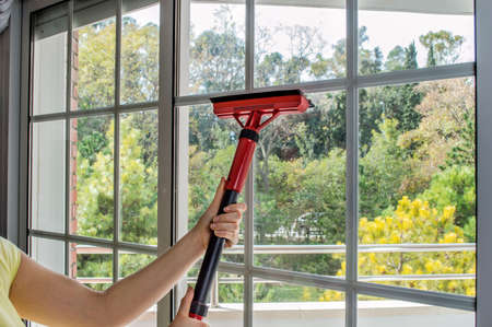 woman cleaning window glass with steam