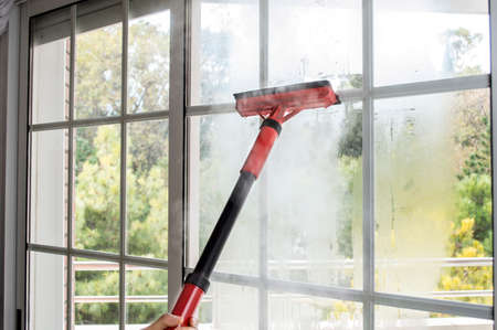 woman cleaning window glass with steam photo
