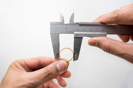 Goldsmith measuring gold ring with vernier caliper photo