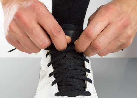 close up of sportsman tying shoelaces photo