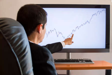 businessman pointing to invest is looking graph on the screen photo