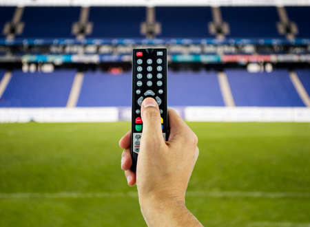 Hand holding television remote for watching sports in 3D photo