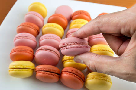 hands catching a big plate of macarons photo