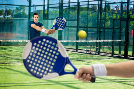 men playing paddle tennis standing and swatting the ball on court photo