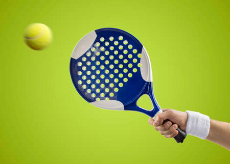 hand with a tennis paddle racket hitting a ball with background green photo