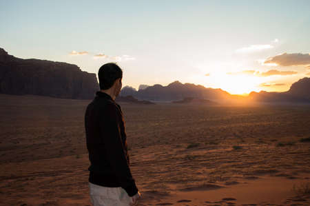 hiker looking at a sunset from a high in the desert of Wadi Rum photo