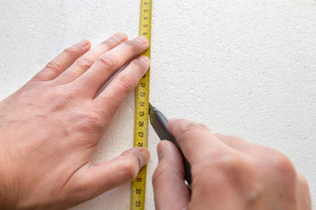 worker cutting polystyrene with a cutter or knife photo