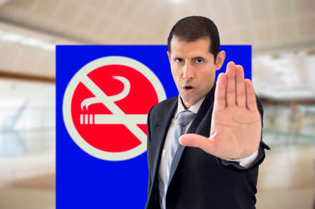 prohibits: security agent prohibits smoking next to a sign in a shopping mall Stock Photo