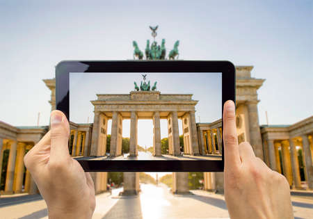 close up of hand photographing a tablet the Brandenburg Gate in berlin photo