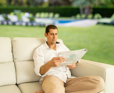 relaxed man reading a newspaper in the garden of his house photo