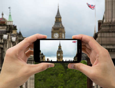 tourist holds up camera mobile at big ben with flag  in london photo