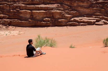 man hiker enjoying view sitting looking over of the desert photo