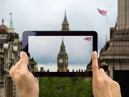 cropped image of a man holding a digital tablet and photographing big ben