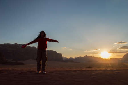 conquered: woman happy hiker with arms raised in air with conquered the desert before sunset Stock Photo