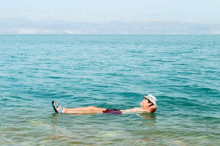 Man floating in a glassy water of dead sea with outstretched arms  Stock Photo