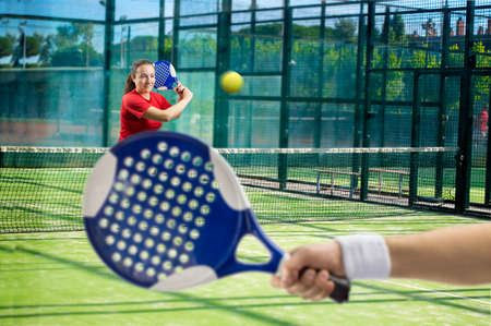 women playing paddle tennis standing and swatting the ball on court photo