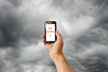 cloud search: hand with a phone searching for signal with a stormy sky