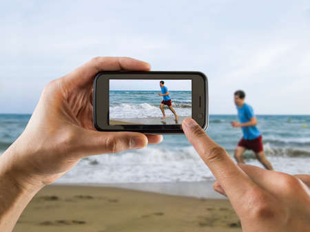 man taking a picture with your mobile phone a one man running for joy on the beach photo