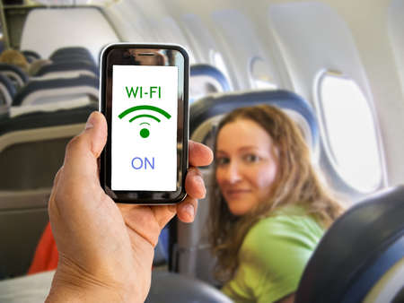 Hand holding mobile smart phone with connect wifi on the airplane Stock Photo