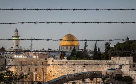 Jerusalem with the wall and the dome protected behind barbed wire at dusk