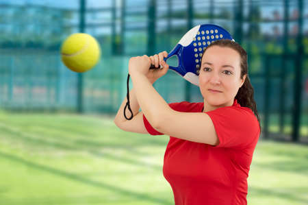 woman hitting the ball with racket paddle in a tennis paddle photo