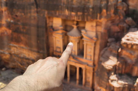 hands pointing to the facade of the al khazneh in petra photo