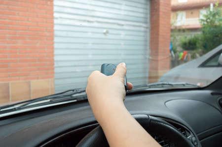 presionando control remoto para entrar en el aparcamiento