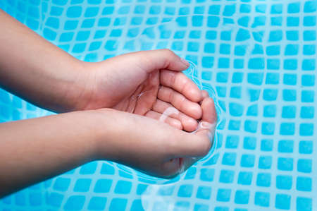 pool preteen: hands of a child taking water from a pool Stock Photo