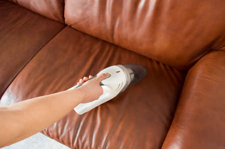 brown leather sofa: woman cleaning the brown sofa with a vacuum cleaner portable Stock Photo