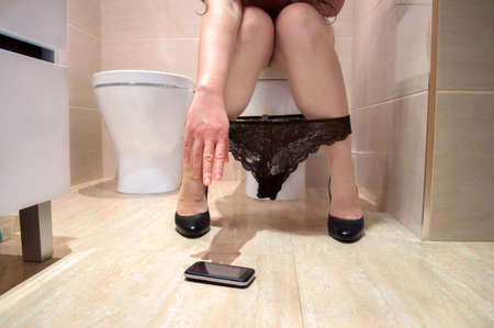 urinating: woman hand holding a phone in the toilet floor