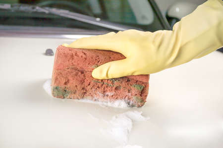 hand hold sponge for washing car with yellow glove inside a parking photo