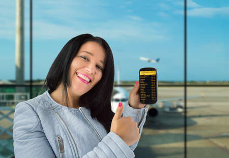 departures board: woman showing her phone with departures board and thumbs up