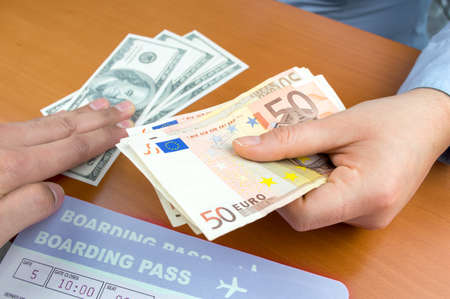 currency exchange: close up a money changing hands of people in an airport