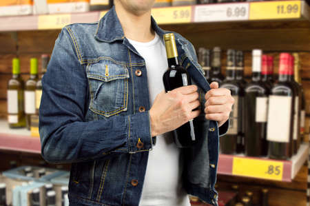 man in a supermarket stealing a bottle of champagne